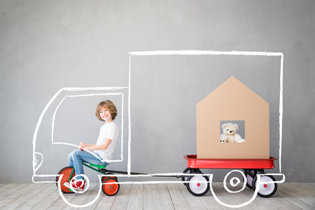Happy child playing into new home. Kid having fun indoor. Moving house day and express delivery concept Stock Photo
