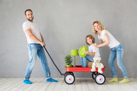 apartment: Happy family playing into new home. Father, mother and child having fun together. Moving house day and express delivery concept Stock Photo