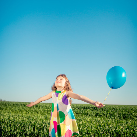 blue green background: Happy child playing with colorful toy balloons outdoors. Smiling kid having fun in green spring field against blue sky background. Freedom concept
