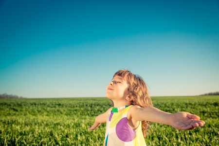 aspirational: Happy child outdoors against blue sky background. Kid having fun in green spring field. Freedom and imagination concept