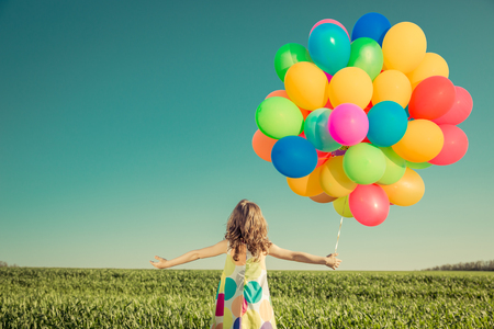 freedom: Happy child playing with colorful toy balloons outdoors. Smiling kid having fun in green spring field against blue sky background. Freedom concept