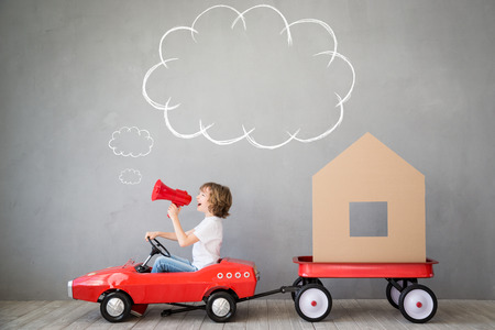 Happy child playing into new home. Kid having fun indoor. Moving house day and express delivery concept Archivio Fotografico