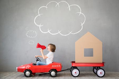 Het gelukkige kind spelen in het nieuwe huis. Jongen plezier binnenshuis. Bewegende dag huis en express-concept Stockfoto - 74509281