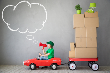 delivery truck: Happy child playing into new home. Kid having fun indoor. Moving house day and express delivery concept Stock Photo