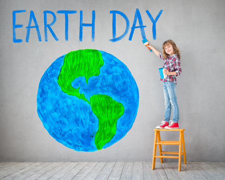 Happy child painting planet on the wall. Kid having fun at home. Spring holiday Earth day concept Standard-Bild