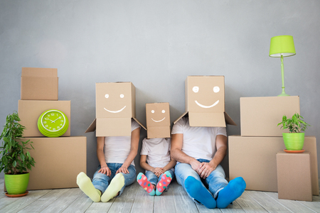 Gelukkige familie die in een nieuw huis speelt. Vader, moeder en kind plezier samen. Bewegende huisdag en 'Think outside the box' concept