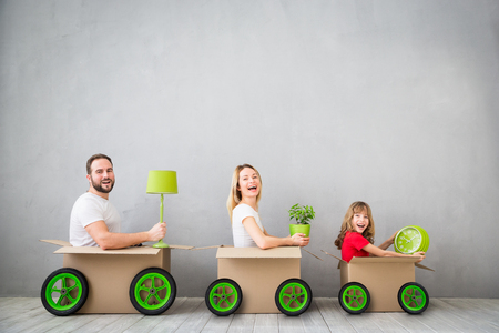 truck: Happy family playing into new home. Father, mother and child having fun together. Moving house day and express delivery concept Stock Photo