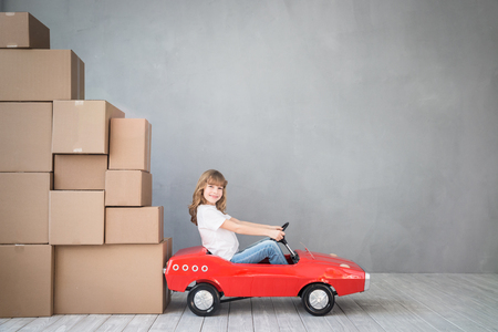 truck: Happy child playing into new home. Kid having fun indoor. Moving house day and express delivery concept Stock Photo