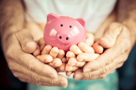 Family holding piggybank in hands. Investment concept Zdjęcie Seryjne - 74972322
