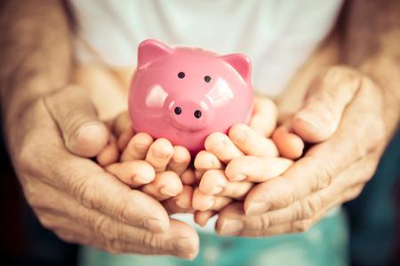 Familie piggybank in handen. investeringen concept