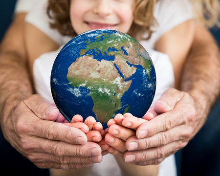 Family holding 3D planet in hands. Earth day holiday concept. Elements of this image furnished by NASA Banco de Imagens