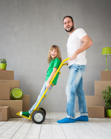 delivery room: Happy family playing into new home. Father and child having fun together. Moving house day and express delivery concept Stock Photo