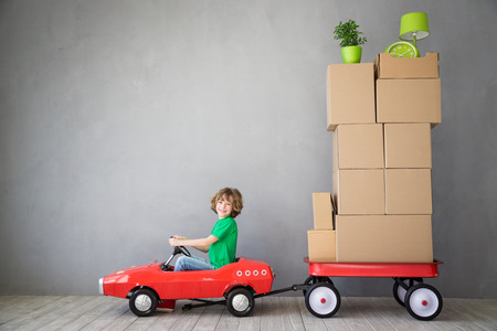 apartment: Happy child playing into new home. Kid having fun indoor. Moving house day and express delivery concept Stock Photo