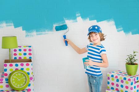 Niño feliz que pinta la pared con el color azul. Cabrito que se divierten en el hogar. concepto de actualización de primavera