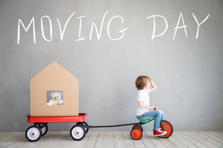 1: Happy child playing into new home. Kid having fun indoor. Moving house day and express delivery concept Stock Photo