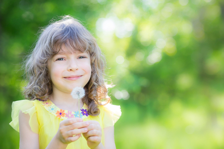 freedom: Happy child blowing dandelion flower outdoors. Girl having fun in spring park. Blurred green background. Dream and imagination concept Stock Photo