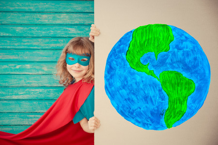 1 person: Superhero child playing at home. Kid hiding behind cardboard banner blank