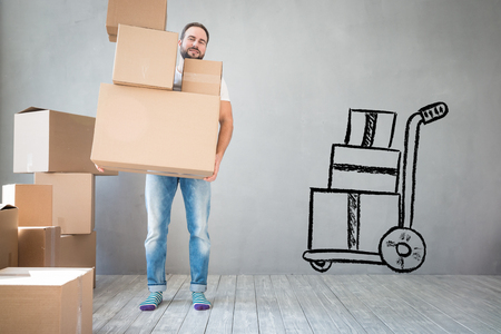 moving truck: Man carrying boxes into new home. Moving house day and express delivery concept