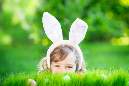 1 person: Easter bunny. Child having fun outdoor. Kid playing with eggs on green grass. Spring holidays concept Stock Photo