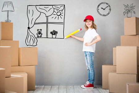 box: Happy child playing into new home. Kid having fun indoor. Moving house day and express delivery concept Stock Photo