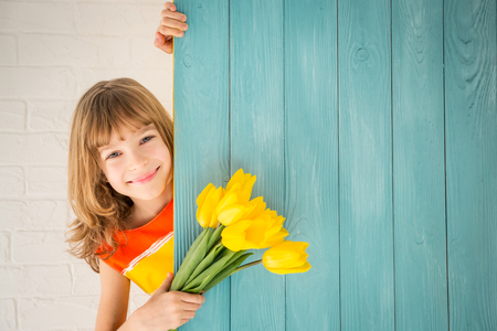 1: Beautiful child with bouquet of flowers hiding behind wooden background. Spring family holiday concept. Mothers day