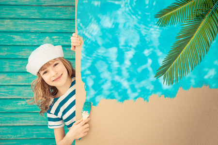 painting: Happy sailor child painting the cardboard with blue color. Kid having fun at home. Spring renovation concept