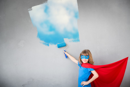 Superhero child painting blue sky on wall. Kid having fun at home. Spring renovation concept