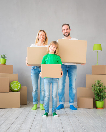 delivery room: Happy family playing into new home. Father, mother and child having fun together. Moving house day and real estate concept Stock Photo