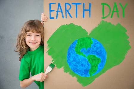 Happy child painting the cardboard with green color. Kid having fun at home. Spring Earth day holiday concept