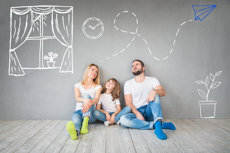 apartment: Happy family sitting on wooden floor. Father, mother and child having fun together. Moving house day, new home and design interior concept Stock Photo