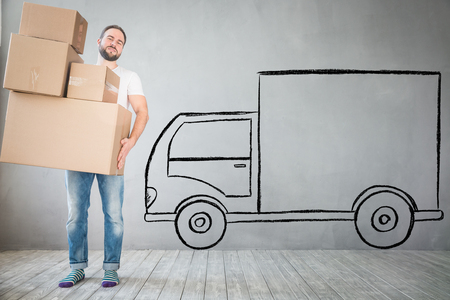 delivery room: Man carrying boxes into new home. Moving house day and express delivery concept