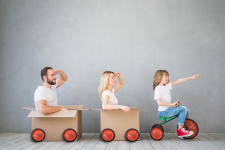 Familia feliz que juega a nuevo hogar. Padre, madre e hijo se divierten juntos. Mueve la casa día y el concepto de entrega urgente Foto de archivo - 75426430