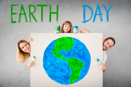 paints: Happy family hiding behind banner blank. Father, mother and child having fun together. Holiday Earth day and spring renovation concept Stock Photo