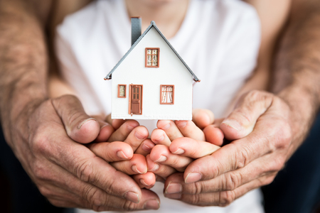 Family holding house in hands. Moving and spring renovation concept Stock Photo - 75802872
