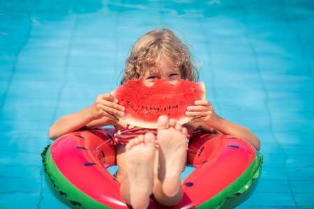 fruit: Child with watermelon outdoor. Kid having fun in swimming pool. Summer vacation and healthy eating concept Stock Photo