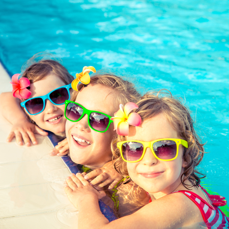 Happy children in the swimming pool. Funny kids playing outdoors. Summer vacation concept Stok Fotoğraf - 75802907