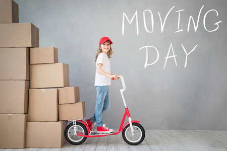 delivery room: Happy child playing into new home. Kid having fun indoor. Moving house day and express delivery concept Stock Photo