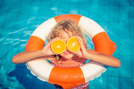 Child with orange outdoor. Kid having fun in swimming pool. Summer vacation and healthy eating concept