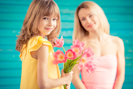 Woman and child with bouquet of flowers against green background. Spring family holiday concept. Mothers day