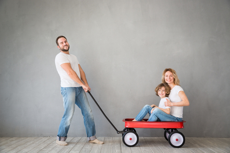 moving box: Happy family playing into new home. Father, mother and child having fun together. Moving house day and express delivery concept Stock Photo
