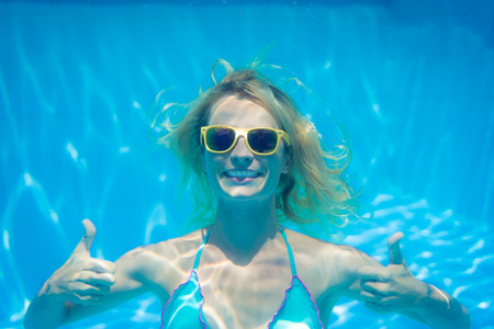 Underwater portrait of woman. Girl having fun in swimming pool. Summer vacation concept