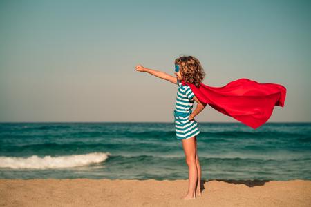 ビーチでスーパー ヒーローの子。スーパー ヒーロー子供の屋外の楽しい時を過します。夏の休暇の概念