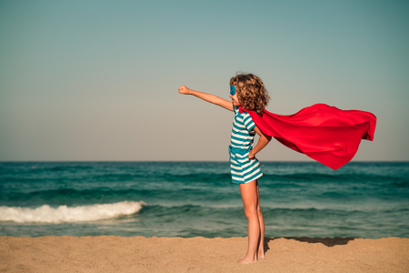 Superhero child on the beach. Super hero kid having fun outdoor. Summer vacation concept