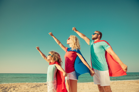 Family of superheroes on the beach. People having fun outdoor. Summer vacation concept