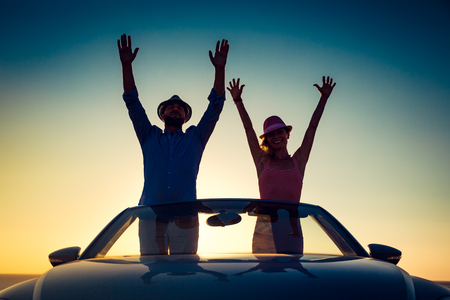 cabrio: Silhouette of happy couple at the beach against sunset sky and sea background. People traveling by car. Summer vacation and travel concept