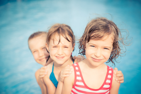 freedom: Happy children in the swimming pool. Funny kids playing outdoors. Summer vacation concept