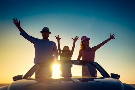 Silhouette of happy family at the beach against sunset sky and sea background. People traveling by car. Summer vacation and travel concept