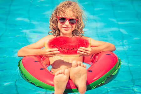 Child with watermelon outdoor. Kid having fun in swimming pool. Summer vacation and healthy eating concept Stock Photo