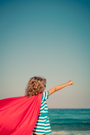 aspirational: Superhero child on the beach. Super hero kid having fun outdoor. Summer vacation concept