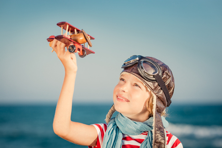 aspirational: Happy child playing with toy airplane against sea and sky background. Kid pilot having fun outdoor. Summer vacation and travel concept. Freedom and imagination